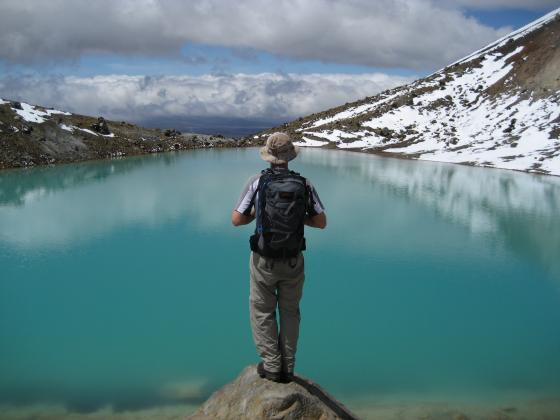 A hiker gazes at an Emerald Lake at Tongariro